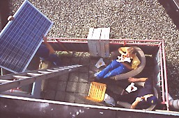 part of installation team taking a break while another member starts carrying a solar panel up the ladder towards the flat roof